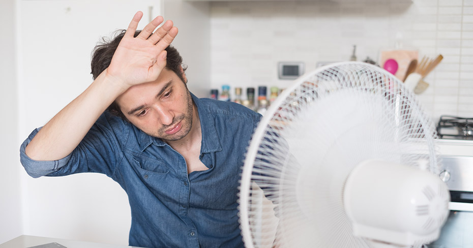 Man sitting in front of an oscillating fan