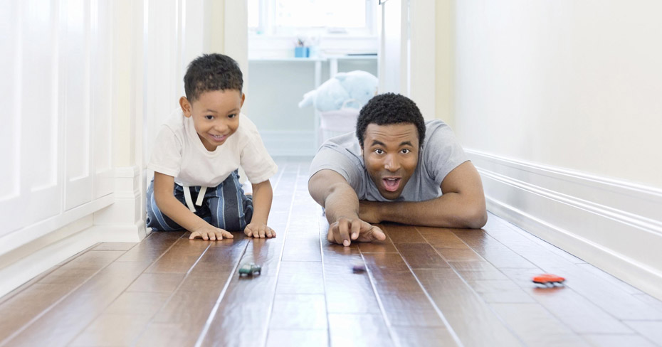 Father and son playing with cars on the floor
