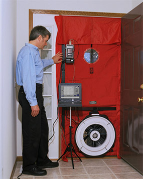 HVAC technician performing blow door test
