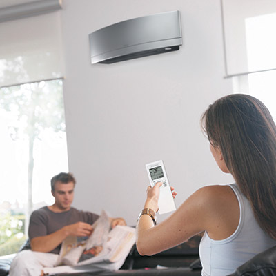 woman adjusting her ductless air conditioner with a remote